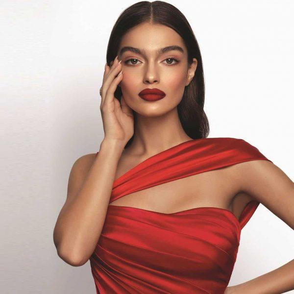 woman modeling her new premier dead sea red lipstick